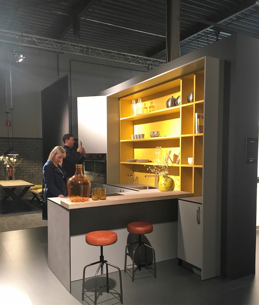 People looking at a Keller kitchen with grey units and a bright yellow shelving unit