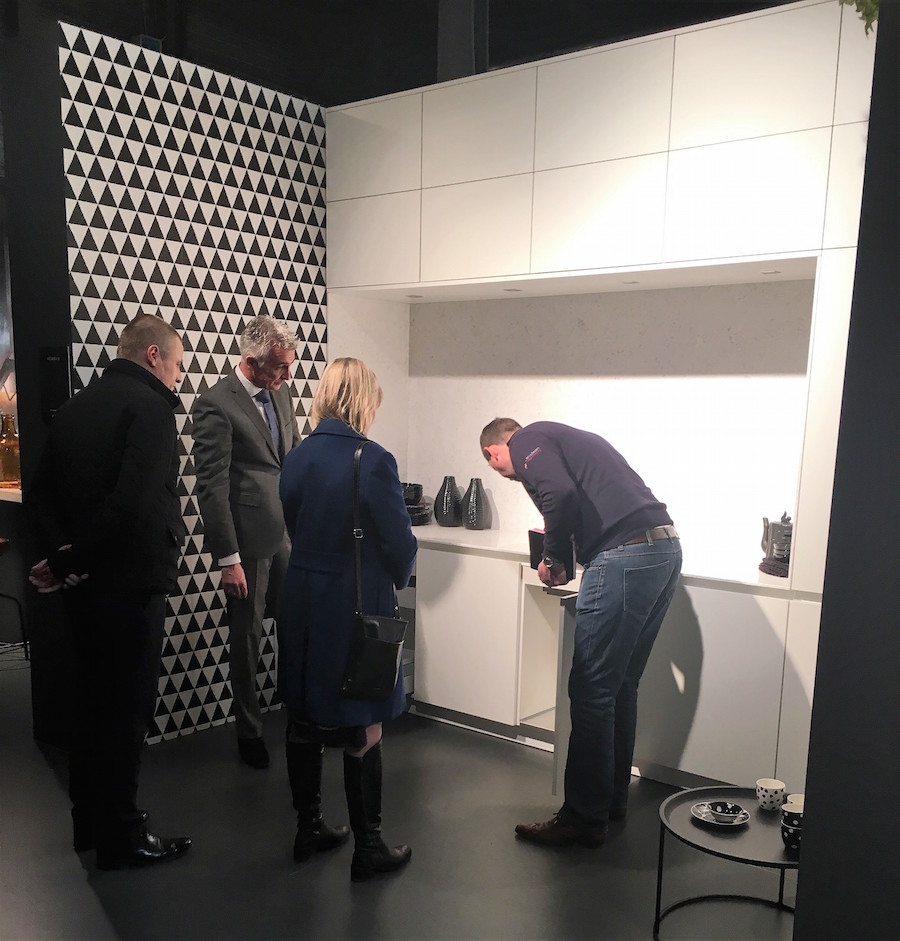 A group of people looking at a gloss white kitchen display